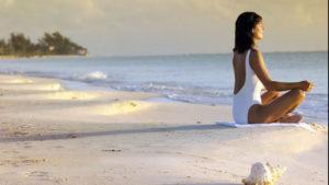 Photo of woman meditating on the beach